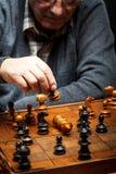 考虑他的在一盘棋的接下来的步骤的老人 免版税图库摄影