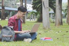 考虑coursework战略的亚裔可爱的男学生 图库摄影