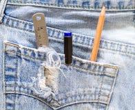 统治者、笔和铅笔在蓝色牛仔裤支持口袋 免版税图库摄影