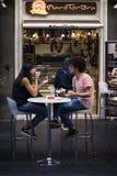 而他们吃沙子,男孩和女孩坐在街道的一张桌上 库存照片