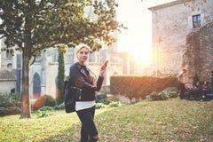 而是常设外部,年轻时髦的女性是固定的单元电话 免版税图库摄影