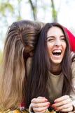 耍笑和笑,在公园的两个朋友 免版税库存图片