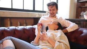 耍笑愉快的夫妇在家以前有在倾斜在人和拿着红色shebel的沙发在客厅,妇女的性  股票视频