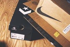 耐克和相反的箱子在地板上 图库摄影