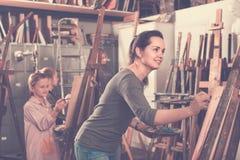 耐心地工作在绘画类期间的学生在艺术演播室 图库摄影