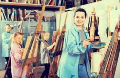 耐心地工作在绘画类期间的学生在艺术演播室 库存照片
