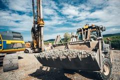 耐用在高速公路建造场所的推土机移动的石渣 在建造场所的多套工业机械 图库摄影