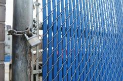 耐用挂锁和链子在蓝色安全门 免版税库存照片
