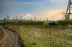 耕与尘土足迹的拖拉机一个领域  免版税库存照片