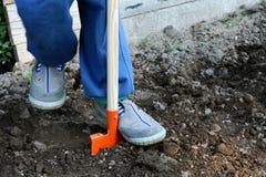 耕种与橙色玩具锹的灰色鞋子的孩子土壤 图库摄影