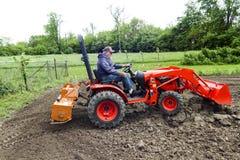 耕种他的有一台紧凑4x4拖拉机的更老的绅士庭院 免版税库存图片