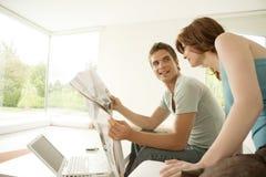 耦合家庭报纸共享 免版税图库摄影