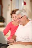 耦合家庭膝上型计算机放松的前辈 免版税库存照片