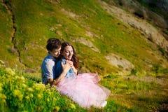 耦合本质 愉快的夫妇坠入爱河在开花的草坪下 免版税图库摄影