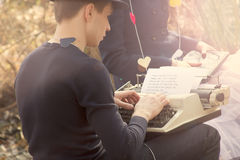 耦合自由职业者的打字机键入的年轻人 免版税库存图片