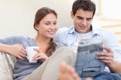 耦合读新闻,当位于在沙发时 免版税库存图片