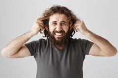 耳朵从听力谎言是疲乏 被打扰的和沮丧的成熟人演播室射击有胡子和卷发拉扯的 图库摄影
