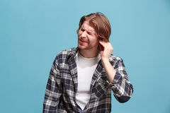 耳朵疼痛 充满头疼或痛苦的哀伤的人在蓝色演播室背景 免版税库存照片