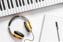 耳机、笔记本和合成器在音乐演播室dj或音乐家工作白色书桌背景顶视图大模型的 免版税库存图片