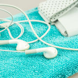 耳机、MP3播放器和turquise现代生活的毛巾标志 库存图片