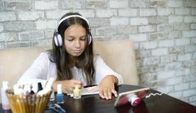 耳机听的音乐的女孩在做修指甲的电话应用指甲油赠送阅本空间 免版税库存图片