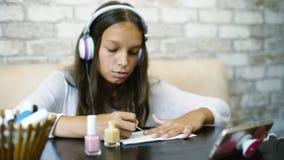 耳机听的音乐的女孩在做修指甲的电话应用指甲油赠送阅本空间 库存照片