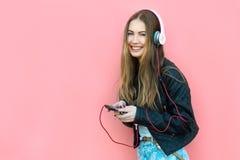 耳机听的音乐的美丽的愉快的妇女在墙壁附近 免版税库存照片
