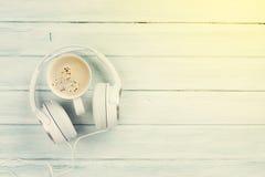 耳机和咖啡杯在木桌上 免版税库存照片