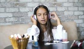 耳机和家庭衣裳听的音乐的逗人喜爱的女孩在电话和唱歌,当做修指甲时 库存图片