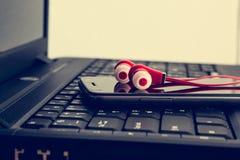 耳机和巧妙的电话在膝上型计算机 免版税图库摄影