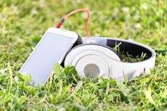 耳机和巧妙的电话在草甸 免版税库存照片