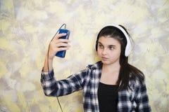 耳机和手机的青少年的女孩 免版税库存照片