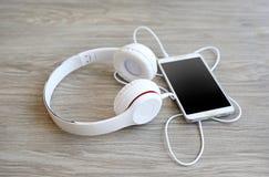 耳机和智能手机在木 免版税图库摄影