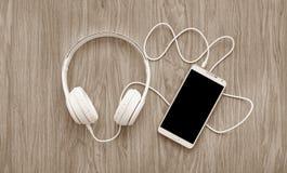 耳机和智能手机在木 库存图片