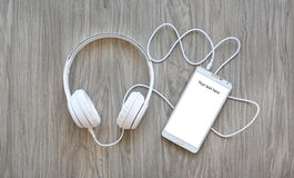 耳机和智能手机有词`的您的这里文本`在白色屏幕上 库存照片