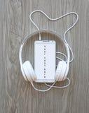 耳机和智能手机有词`的您的这里文本`在白色屏幕上 免版税图库摄影