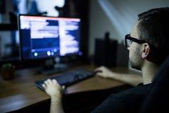 耳机和镜片的黑客有乱砍计算机系统的键盘的 库存图片