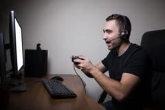 耳机和玻璃的年轻游戏玩家使用控制台和计算机打的比赛 免版税库存图片