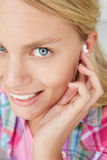 耳机女孩微笑的少年佩带 免版税库存图片