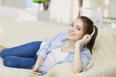 耳机微笑的听的女孩音乐坐室内 免版税库存照片