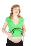 耳机怀孕的俏丽的妇女 免版税库存图片