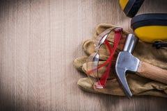 耳机拔钉锤皮革安全手套和防护glas 免版税库存照片