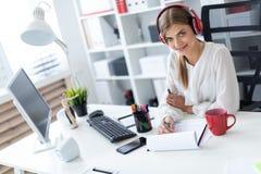 耳机的一个女孩坐在一张桌上在办公室并且画在板料的一个标志 免版税库存照片