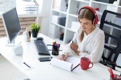 耳机的一个女孩坐在一张桌上在办公室并且画在板料的一个标志 库存图片