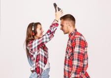 耳机的一个女孩采取耳机灰色背景的一个人 免版税库存图片