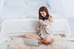 耳机的一个女孩,在毛线衣,坐地板在卧室并且看膝上型计算机 户内 免版税库存照片