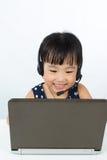 耳机的亚裔矮小的中国女孩有膝上型计算机的 免版税库存图片