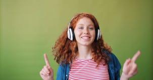 耳机的享受音乐和跳舞的十几岁的女孩画象  股票录像