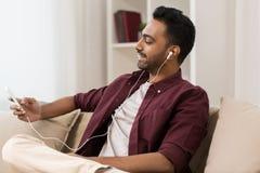 耳机的人听到在智能手机的音乐的 免版税库存图片