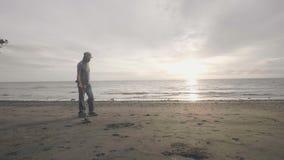 耳机的人工作在海滩的扫描的沙子与金属探测器发现贵重物品的在日出 股票视频